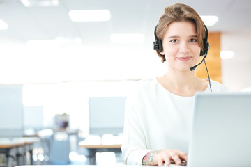 Smiling woman customer support call operator in office