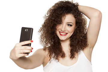 beautiful girl with curly hair takes selfies
