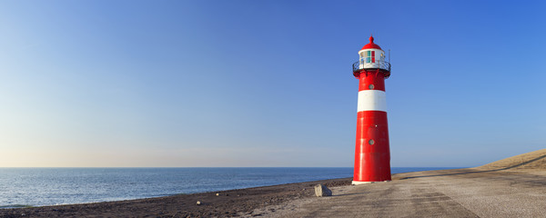 Fotobehang Vuurtoren Red and white lighthouse and a clear blue sky
