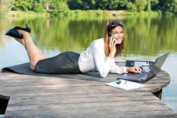 Geschäftsfrau mit Arbeitsplatz am Teich - Home Office