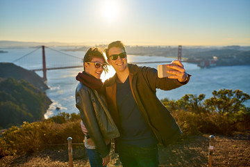 traveling couple taking a selfie shot in front of golden gate bridge