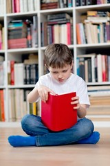 Little boy child reading a red book in the library.