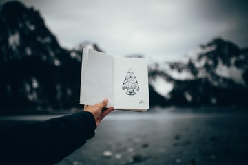 Person holding a book in the mountains