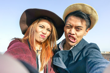 Hipster asian couple making selfie with funny faces