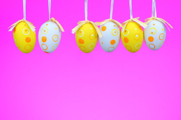 Easter eggs on rope on colorful wooden background. Easter backgr