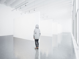 Photo of girl in empty modern gallery looking at the blank white canvas. Big windows, spotlights, concrete floor. Horizontal, mockup