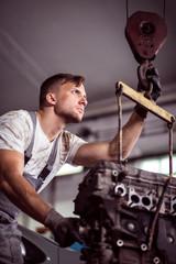Car mechanic fixing automotive motor