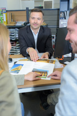 Salesman showing housing brochure to couple