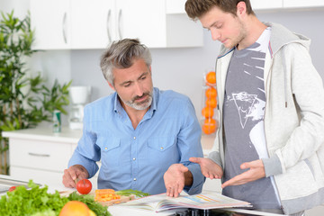 Man chopping vegetables, discussing content of book
