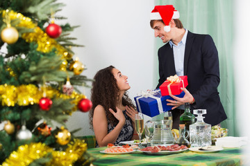 Man giving present to happy  woman during Christmas dinner