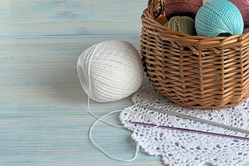 Knitting.   Crochet doily and balls of colored cotton yarn in a basket on a blue wooden background.