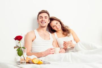 Happy couple in love having romantic breakfast in bedroom