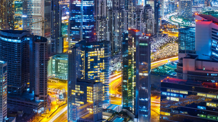 Fantastic rooftop view of a big modern city architecture at night with roads. Business bay, Dubai, United Arab Emirates.