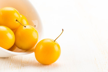 Handful of yellow cherry plums in ceramic bowl - isolated on white background