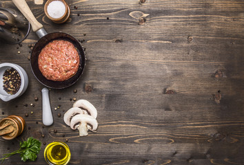 cutlet of ground beef in a small frying pan, sliced mushrooms, pepper, herbs and salt border ,place for text on wooden rustic background top view close up