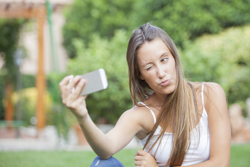 Close up portrait of a young attractive woman holding a smartphone digital camera with her hand and taking a funny self portrait