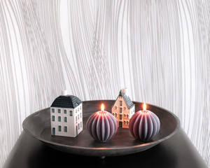 Still life of black metal tray with two ribbed candles and houses.