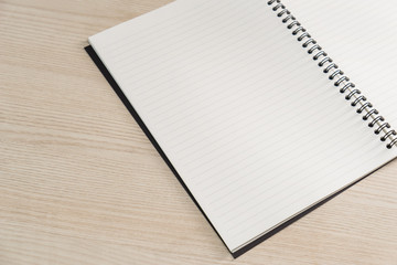 Open notebook with white lined pages on wooden office desk .