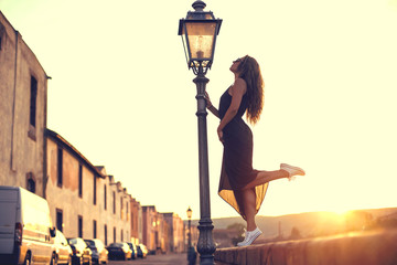 Young pretty woman in black dress, sunglasses and white sneakers at sunset in Italy.