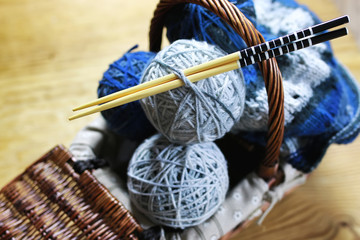 balls of wool and knitting needles on background