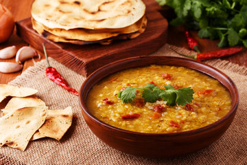 .Thick indian red lentil soup with cilantro served with indian f