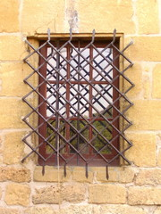 Medieval mullioned window with an ornate wrought iron security grill.