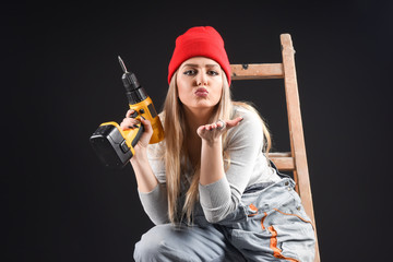 The sexy blond woman holds an electric drill and wearing red hat