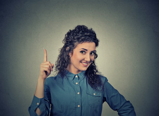 young woman has idea, pointing with finger up looking happy
