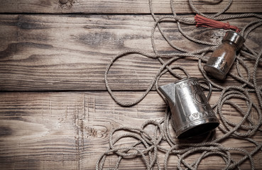 Rope, spices and metal utensils on old wooden burned table or bo
