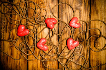 Rope and red hearts on old wooden burned table or board for back