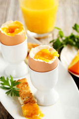 Boiled egg with toasts on a grey wooden table