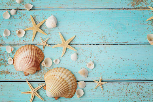 seashells and sand on wooden background