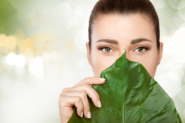 Gorgeous young woman with a fresh leaf to her face