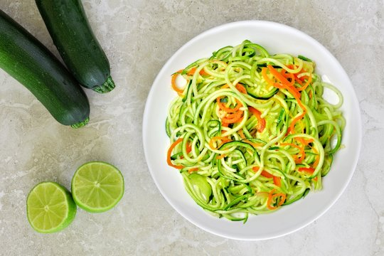 Healthy zucchini noodle dish with carrots and lime on white marble background, overhead view