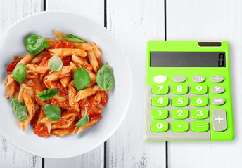 Calculator and delicious pasta with tomato sauce on wooden background