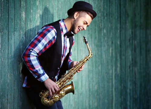 Young man playing on saxophone outside near the old wall