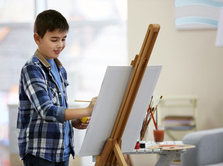 Little boy drawing on easel at home