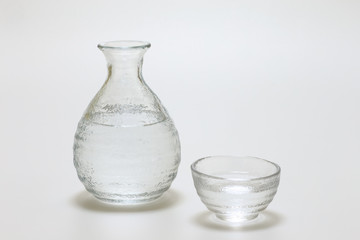 Sake cup and bottle on white background
