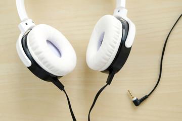 White headphones on wood background