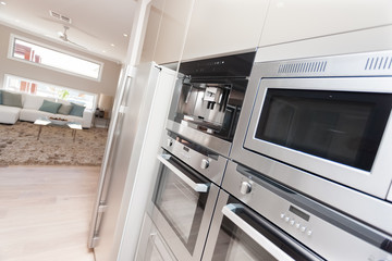 Closeup of modern ovens and a refrigerator in the luxurious kitc