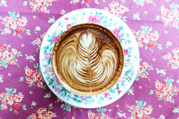 cup of latte art coffee on background texture fabric floral pattern.