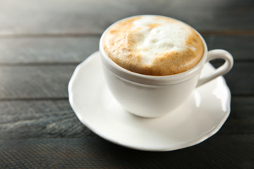 Cup of hot cappuccino with froth on a black wooden table
