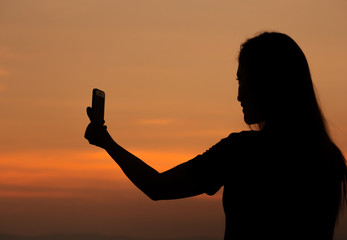 Silhouette of woman taking photo with mobile phone