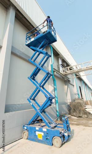 Builder on a Scissor Lift Platform at a construction site  Men at