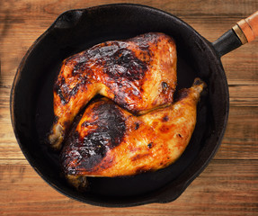 Roasted chicken legs on a cast iron skillet.