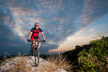 Happy man on a mountain bike races downhill in the nature against blue cloudy evening sky. Cyclist is wearing red sportswear helmet gloves and red glasses. Cross country biking.