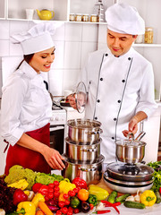 Happy man and woman professional in chef hat cooking at kitchen.