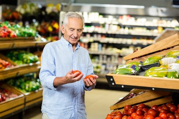 Senior man looking at two tomatoes