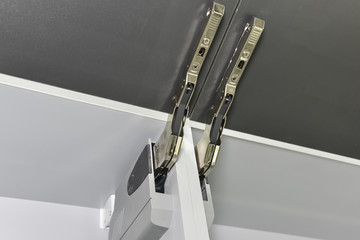 Closeup detail of a hinge on kitchen cupboard