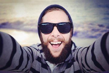 Composite image of portrait of happy hipster wearing sunglasses